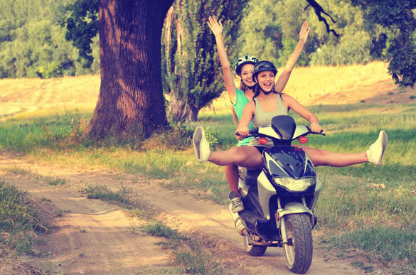 Two teenage girls riding motorcycle on the countryside