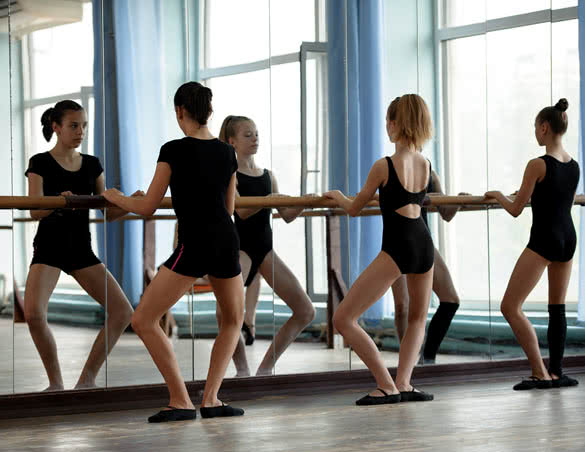 Three ballet dancers doing plie exercise
